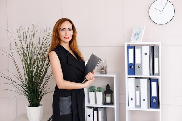 Geschäftsfrau mit einem papierordner in der nähe der regale mit geschäftspapieren