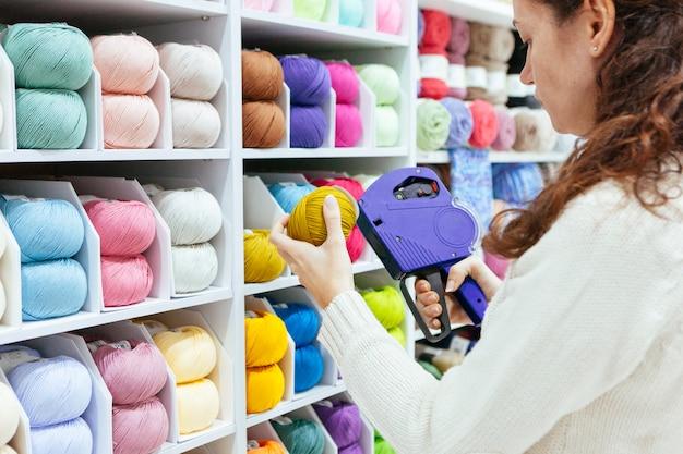 Geschäftsfrau mit einer etikettiermaschine, die produkte auf verkauf aktualisiert