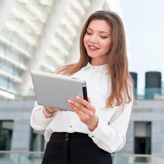 Geschäftsfrau mit einer tablette in der straße