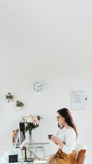 Geschäftsfrau mit einer tasse kaffee im büro