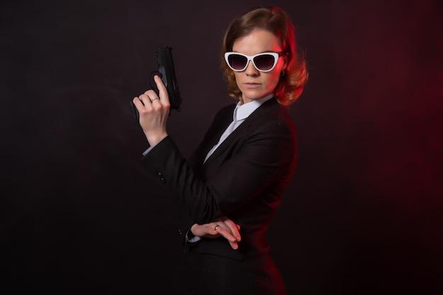 Geschäftsfrau mit einer waffe in der hand. porträt auf einer schwarzen wand