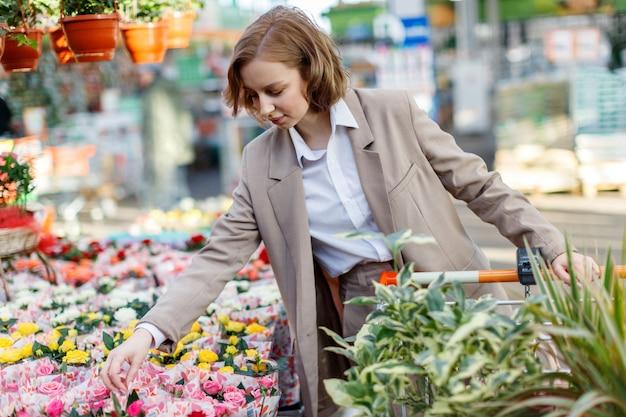 Geschäftsfrau mit einkaufswagenauswahl, kauf von pflanzen für ihr haus im gartencenter.