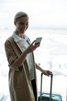 Geschäftsfrau mit gepäck mit handy