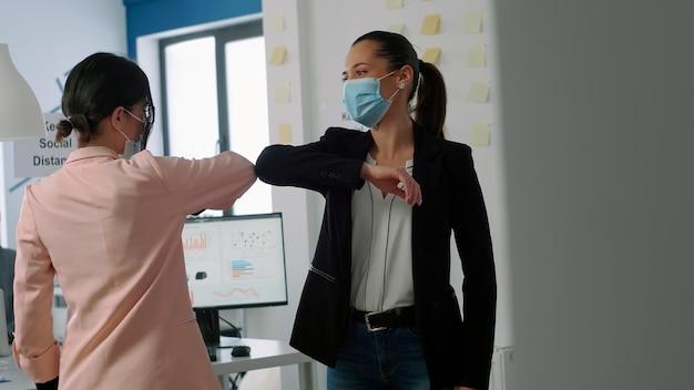Geschäftsfrau mit gesichtsmaske, die den ellbogen berührt, um eine infektion mit dem coronavirus zu verhindern. während der arbeit im firmenbüro. mitarbeiter respektieren die soziale distanzierung während der globalen pandemie von covid19