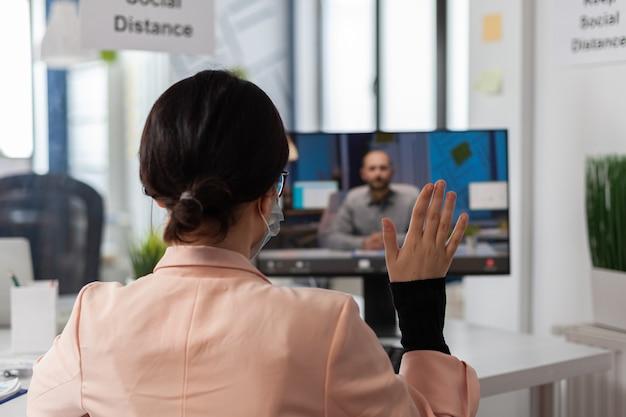 Geschäftsfrau mit gesichtsmaske, die den remote-manager begrüßt und die unternehmensstrategie diskutiert