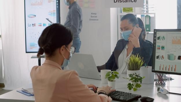 Geschäftsfrau mit gesichtsmaske, die finanzberichte überprüft, während ihr kollege am telefon spricht, der im firmenbüro sitzt. mitarbeiter halten soziale distanz ein, um viruserkrankungen zu vermeiden