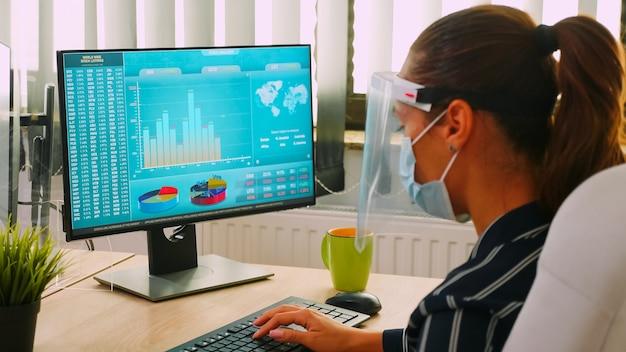 Geschäftsfrau mit gesichtsmaske, die während der coronavirus-pandemie am computer arbeitet und finanzstatistiken in einem neuen normalen geschäftsbüro analysiert, das die soziale distanz respektiert. freiberufler mit moderner technologie