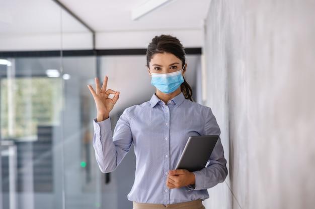 Geschäftsfrau mit gesichtsmaske, die während des coronavirus fest mit tablette steht und okay zeichen zeigt.