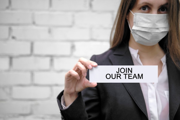Geschäftsfrau mit gesichtsmaske hält ein schild mit der aufschrift join our team auf weißem ziegelsteinwandhintergrund