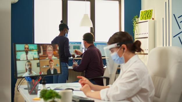 Geschäftsfrau mit gesichtsmaske im büro, die während der coronavirus-epidemie per videoanruf mit dem remote-team spricht. manager, der eine online-konferenz abhält, während kollegen unter einhaltung der sozialen distanz arbeiten