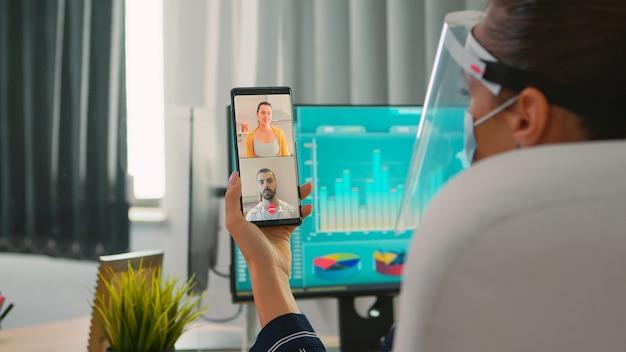 Geschäftsfrau mit gesichtsschutz gegen coronavirus, die per videoanruf mit dem remote-team auf dem smartphone in einem neuen normalen büro spricht. freiberufler, der in einem finanzunternehmen arbeitet und die soziale distanz respektiert