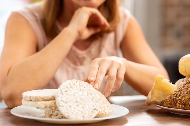 Geschäftsfrau mit glutenallergie, die glutenfreie chips zum abendessen wählt