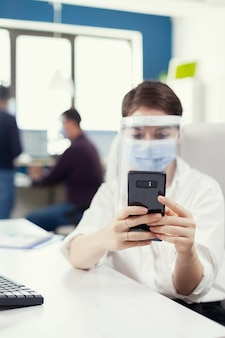 Geschäftsfrau mit handy-sms auf dem smartphone mit gesichtsmaske als sicherheitsvorkehrung gegen covid19. multiethnische mitarbeiter, die in finanzunternehmen unter wahrung der sozialen distanz arbeiten.