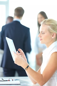 Geschäftsfrau mit ihrem digitalen tablet mit firmen, die mit unscharfen hintergrund