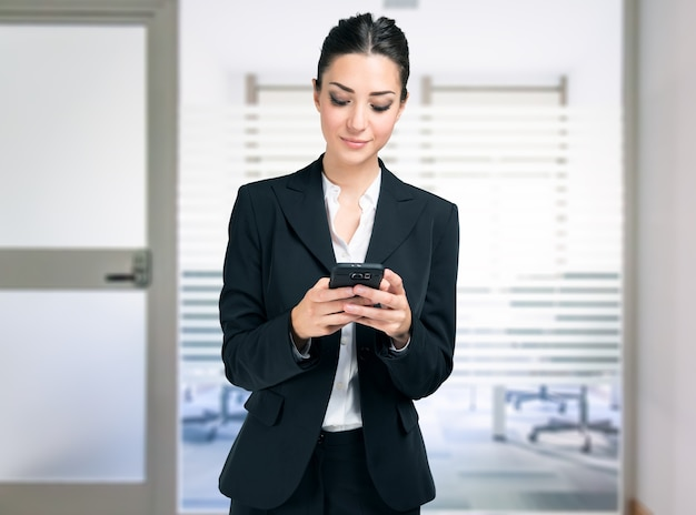 Geschäftsfrau mit ihrem handy im büro
