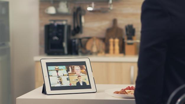 Geschäftsfrau mit intelligentem gerät beim frühstück in der küche. junge freiberuflerin, die zu hause mit ihren kollegen aus dem büro per videoanruf spricht und moderne internettechnologie nutzt