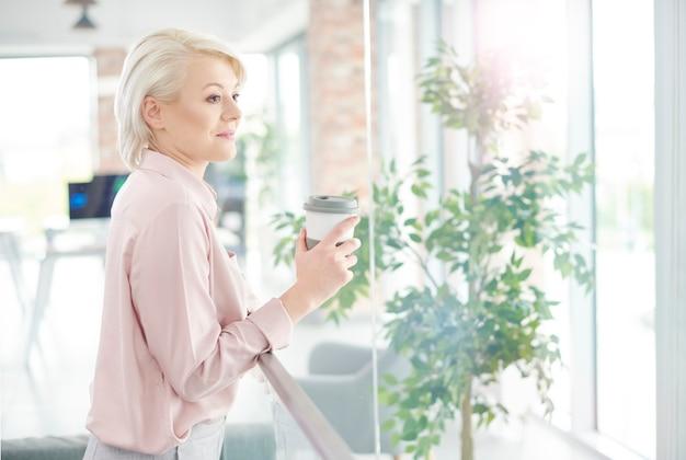Geschäftsfrau mit kaffee, der durch das fenster schaut