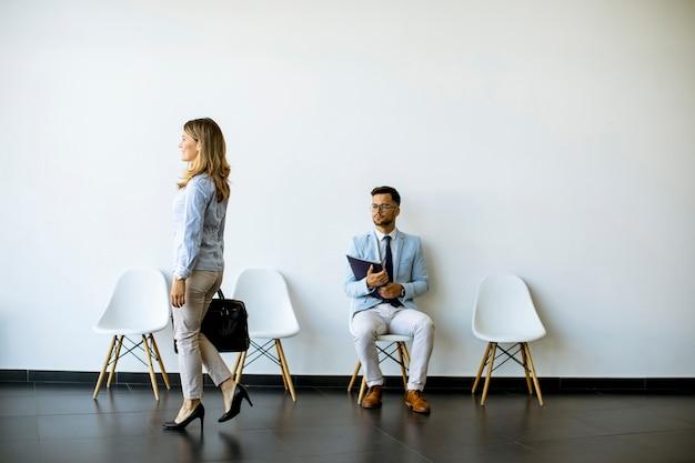 Geschäftsfrau mit koffer vorbei an jungem mann, der am stuhl im wartezimmer mit einem ordner in der hand vor einem interview sitzt