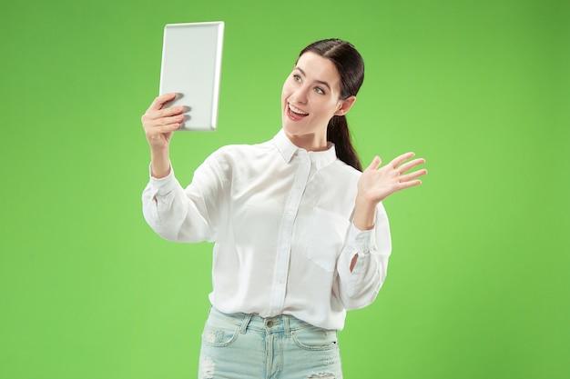 Geschäftsfrau mit laptop. attraktives weibliches vorderes porträt der halben länge, trendiger grüner studiohintergrund. junge emotionale hübsche frau.