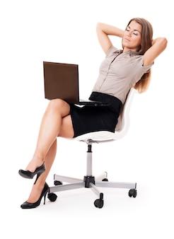 Geschäftsfrau mit laptop, der auf bürostuhl entspannt