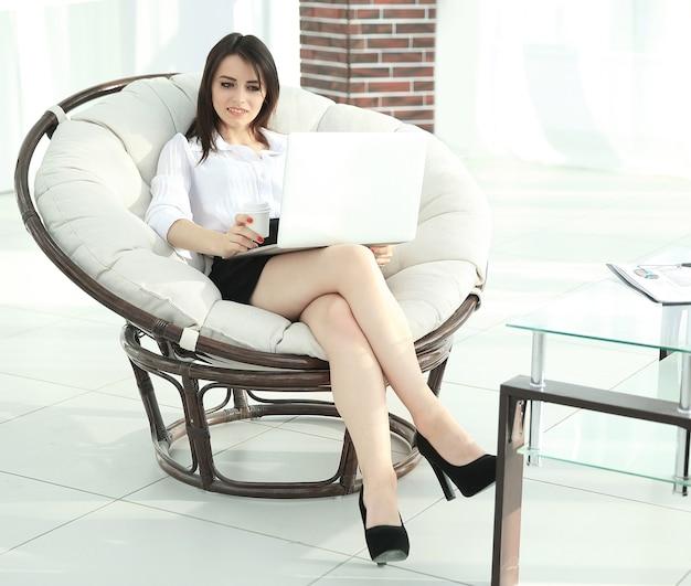 Geschäftsfrau mit laptop, der in einem bequemen stuhl sitzt.