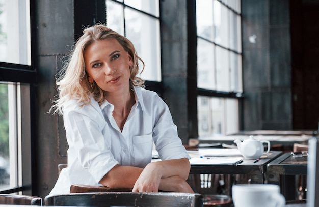Geschäftsfrau mit lockigem blondem haar drinnen im café tagsüber.