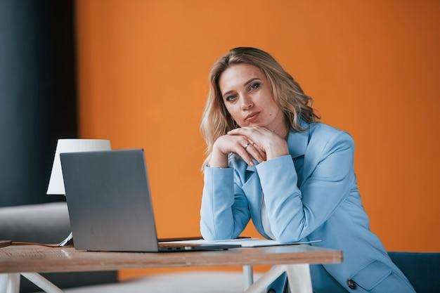 Geschäftsfrau mit lockigem blondem haar drinnen im raum mit orangefarbener wand und holztisch.