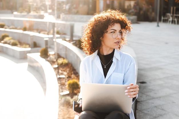 Geschäftsfrau mit lockigem haar, die draußen am laptop für mode-lifestyle-design-mobilkommunikation arbeitet...
