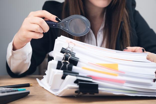 Geschäftsfrau mit lupe und dokumenten