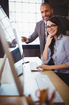Geschäftsfrau mit männlichem kollegen am computertisch