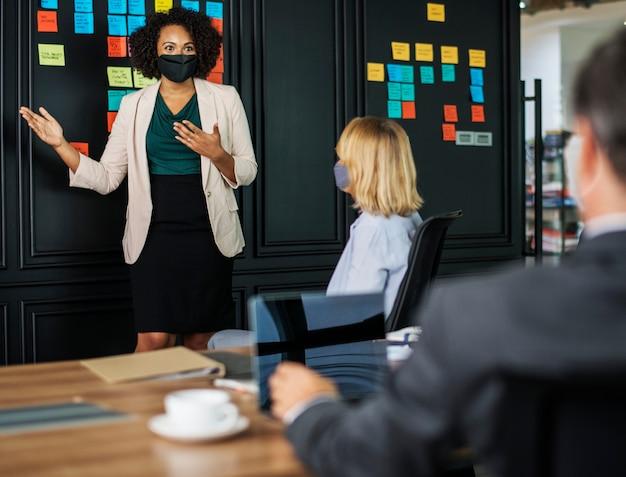 Geschäftsfrau mit maske beim coronavirus-treffen, der neuen normalität