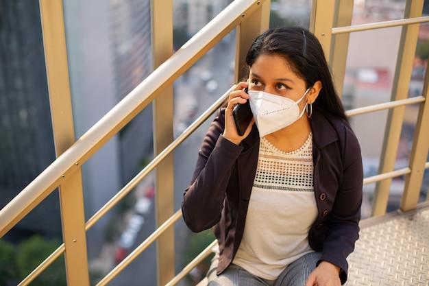 Geschäftsfrau mit maske, die sie auf mahlzeitentreppen sitzt und am telefon spricht