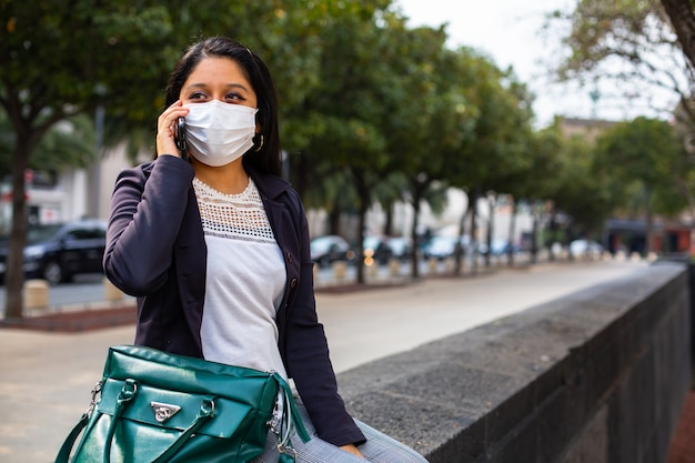 Geschäftsfrau mit maske, die sie sitzt und am telefon spricht