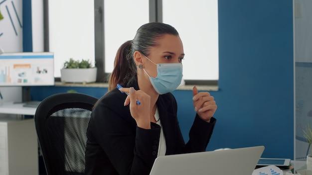 Geschäftsfrau mit medizinischer gesichtsmaske, die mit ihrem team über kommunikationsstrategie am schreibtisch spricht. das geschäftsteam hält die soziale distanzierung aufrecht, während es in einem neuen normalen firmenbüro arbeitet