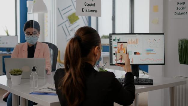 Geschäftsfrau mit medizinischer gesichtsmaske, die über ein videoanruf-meeting mit einem leitenden freiberufler unter verwendung eines modernen smartphones spricht. kaukasische frau, die während covid19 auf dem schreibtisch im firmenbüro sitzt