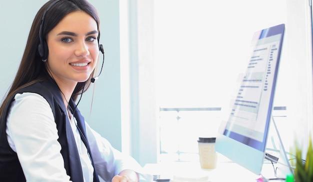 Geschäftsfrau mit mikrofon-headset mit computer im büro - betreiber, callcenter.