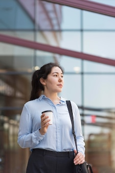 Geschäftsfrau mit niedrigem winkel, die kaffee hält