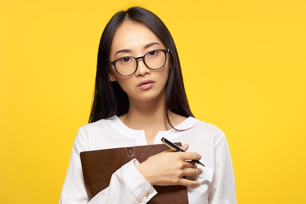 Geschäftsfrau mit notizbuchhänden und gelbem hintergrund des stiftbüro-managers. hochwertiges foto