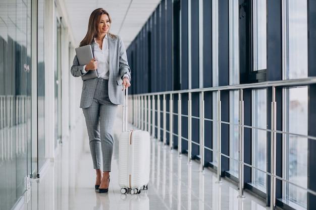 Geschäftsfrau mit reisegepäck im flughafen, laptop haltend