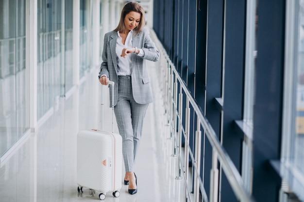 Geschäftsfrau mit reisetasche im flughafen, die auf einen flug wartet