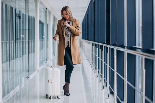 Geschäftsfrau mit reisetasche im flughafen