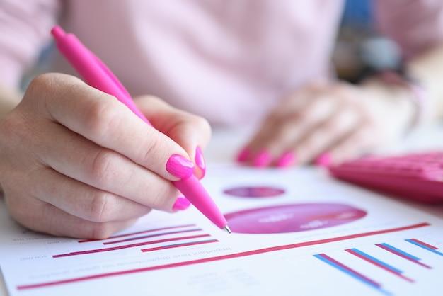 Geschäftsfrau mit rosa nägeln, die mit stift in dokumenten mit diagrammnahaufnahme schreiben