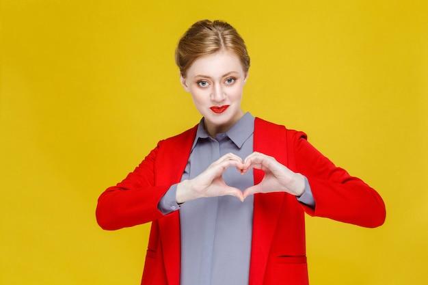 Geschäftsfrau mit roten haaren im roten anzug, die herzformzeichen zeigt