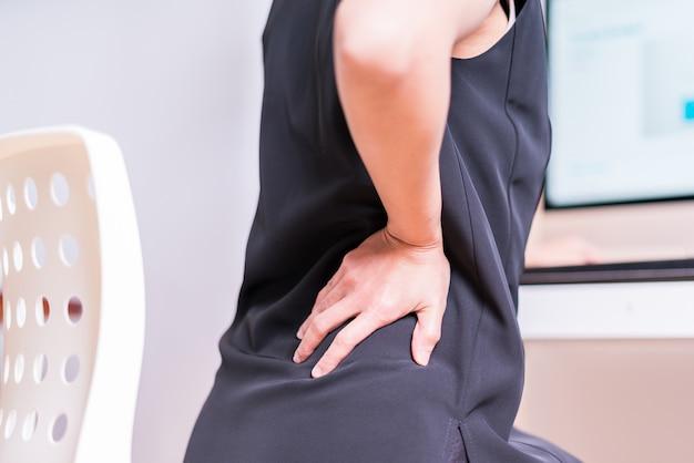 Geschäftsfrau mit rückenschmerzen ein büro. gesundheitswesen und medizinisches konzept