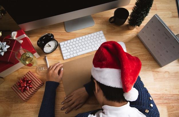 Geschäftsfrau mit sankt-hut schlafend auf schreibtischbüro nach weihnachtsfest und guten rutsch ins neue jahr.