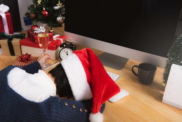 Geschäftsfrau mit sankt-hut schlafend auf schreibtischbüro nach weihnachtsfest