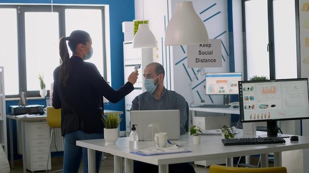 Geschäftsfrau mit schützender gesichtsmaske, die die teamtemperatur mit einem medizinischen thermometer überprüft. mitarbeiter respektieren soziale distanz im neuen normalen firmenbüro, um eine infektion mit viruserkrankungen zu vermeiden