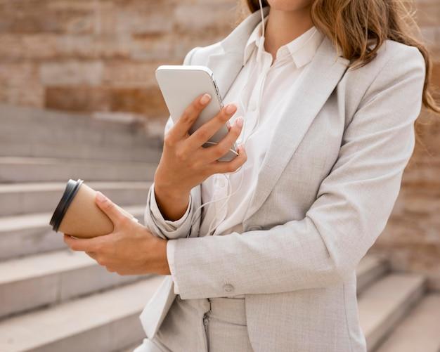 Geschäftsfrau mit smartphone und kaffeetasse im freien