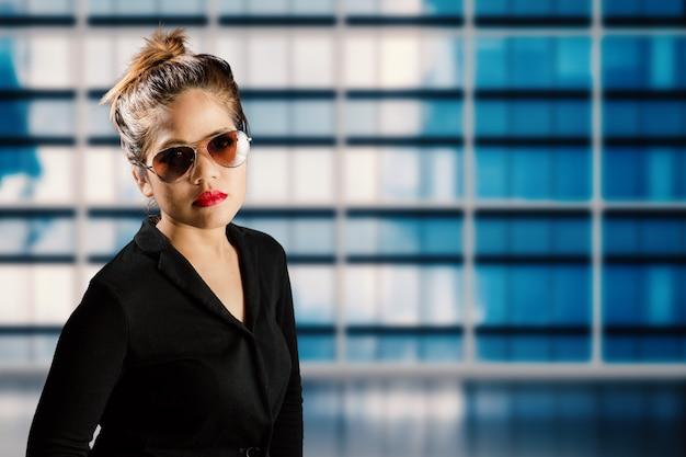 Geschäftsfrau mit sonnenbrille und roten lippen mit gebäudehintergrund