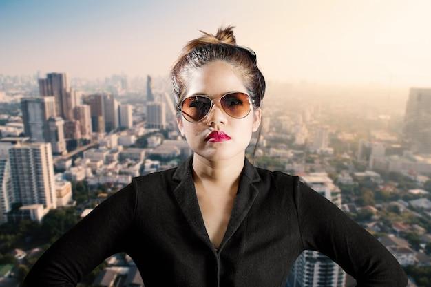 Geschäftsfrau mit sonnenbrille und roten lippen mit stadtbildhintergrund